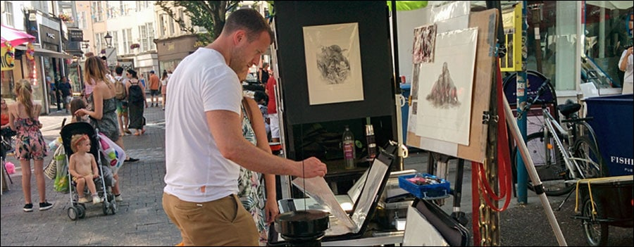 How to spot a buyer Man choosing prints on market stall