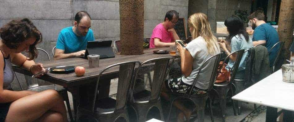All traveling solo, Backpackers all sitting looking at their devices