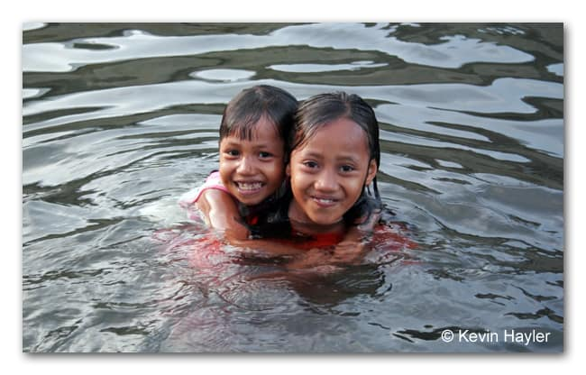 Local Bajo (Sea Gypsy) kids having fun and playing in the water. Togian Islands, Suluwesi, Indonesia. A very cheap budget destination