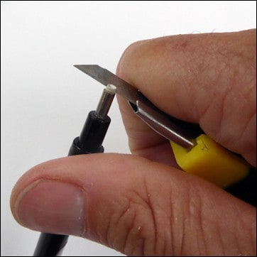 Sharpening the tip of an eraser pen with a craft knife.