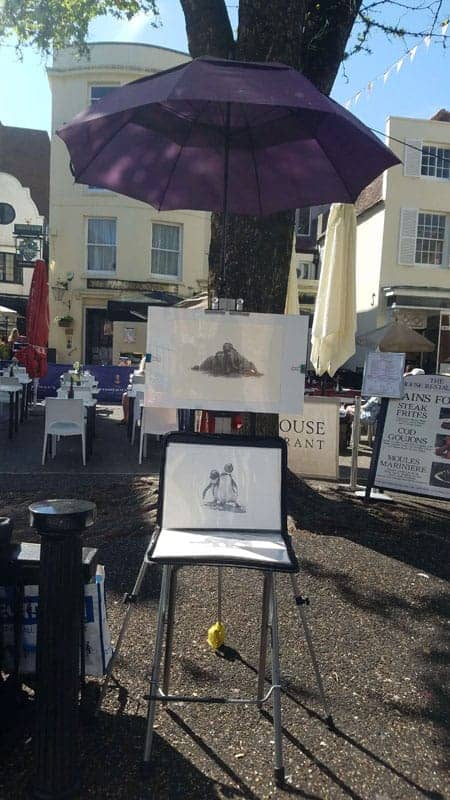 Easel set up. A drawing behind perspex and underneath an umbrella in an outdoor pitch