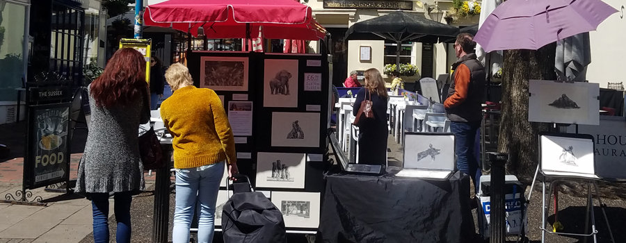 How to prepare for an outdoor art fair feature image. Two ladies buying art on a sunny day