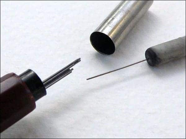 Mechanical pencil top button assembly showing the spare leads, eraser, and wire